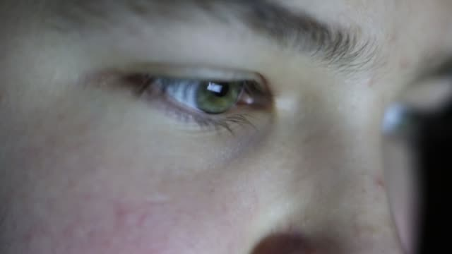 A boy with green eyes looks at the monitor. The eyes of a teenager are shot close-up. hacker stock videos & royalty-free footage