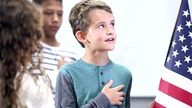 Boy with group in classroom, pledge of allegiance video