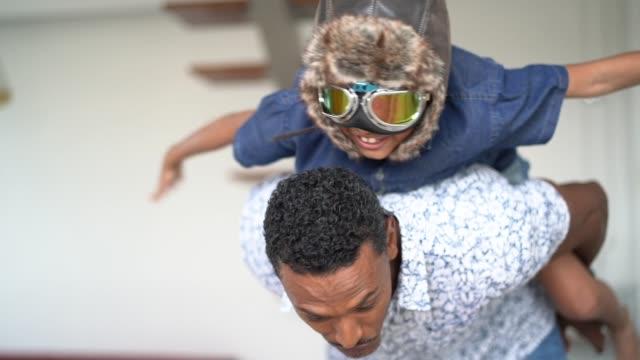 pojke med pilot glasögon leka flyga med sin pappa hemma - föreställningsförmåga bildbanksvideor och videomaterial från bakom kulisserna