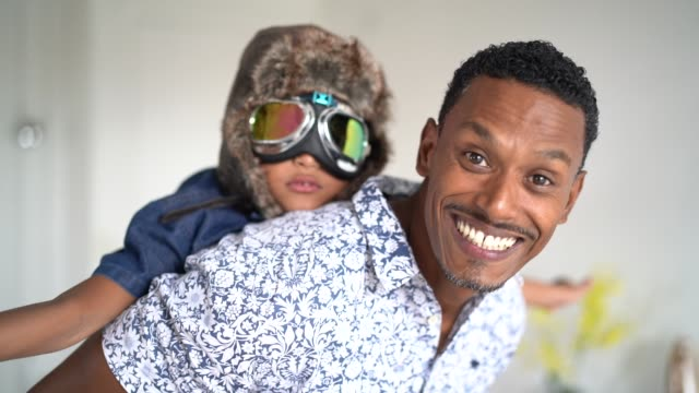 Boy with pilot glasses play fly with his dad at home