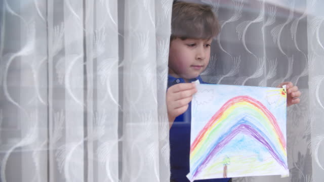 Boy with rainbow painting during COVID-19 lockdown Boy with rainbow painting during COVID-19 lockdown. stay home stock videos & royalty-free footage
