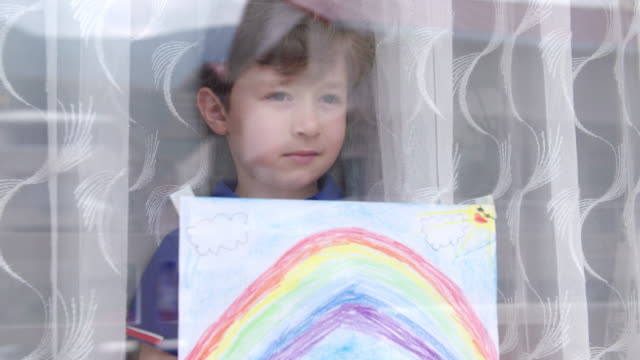 boy with rainbow painting during covid-19 lockdown - vicino video stock e b–roll