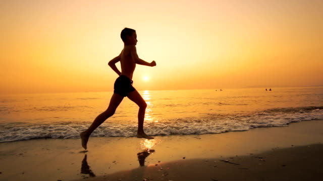 Boy with Reflected silhouette running on the beach during summer vacation at sunset, SLOW MOTION