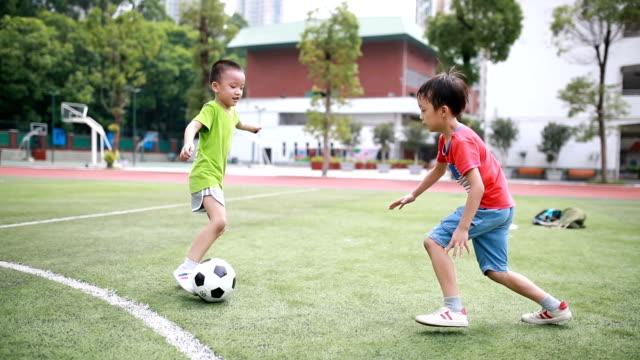 남자아이 있는 축구공 - 풀 벼과 스톡 비디오 및 b-롤 화면