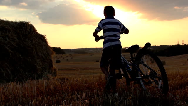 boy with the bicycle in the field at sunset, near haystacks video