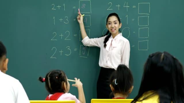 Boy escribe la respuesta del problema de matemáticas en el tablero verde. - vídeo