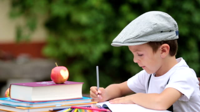 boy, writing his homework from school, drawing and writing in his notebook, learning new things, outdoors - banchi scuola video stock e b–roll