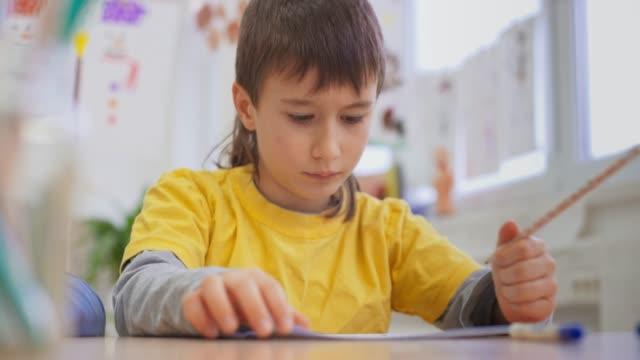 ragazzo che scrive nel suo taccuino nella luminosa classe - 8 9 anni video stock e b–roll