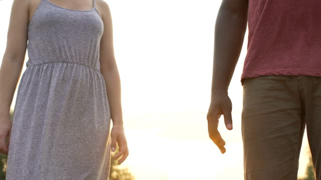 Boyfriend and girlfriend firmly clasp hands on a sunset background, together video