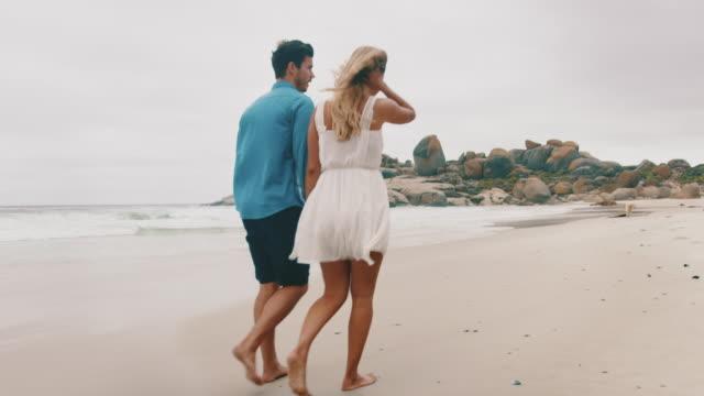 Boyfriend and girlfriend walking at beach