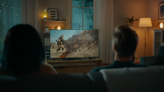 boyfriend and girlfriend watching epic war movie on tv while sitting on a couch at home in the evening. back view shot. - family home video stock e b–roll