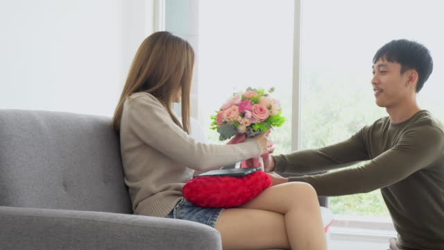 Boyfriend giving the surprise flower to his girlfriend, pan shot