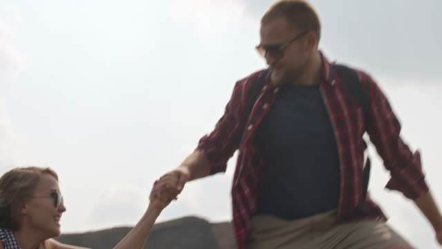 Boyfriend Helping Girlfriend to Climb on Hill Low angle shot with tilt up of middle aged man in sunglasses and checkered shirt helping his blond girlfriend to climb up mound on hiking trip boyfriend stock videos & royalty-free footage