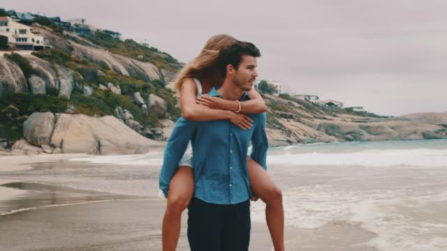 Boyfriend piggybacking girlfriend at beach