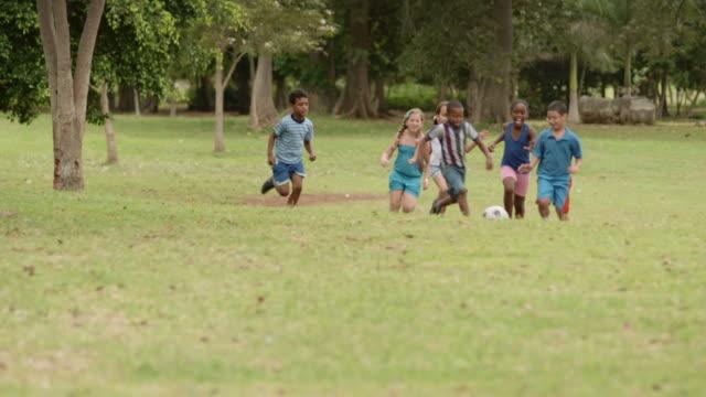jungen und mädchen spielen fußball im park - ferienlager stock-videos und b-roll-filmmaterial