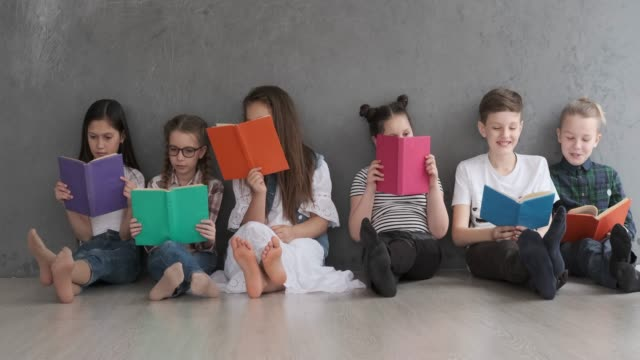 소년과 소녀 책을 읽고 - reading 스톡 비디오 및 b-롤 화면