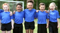 istock Boys and girls soccer team standing in a row, shouting 880776216