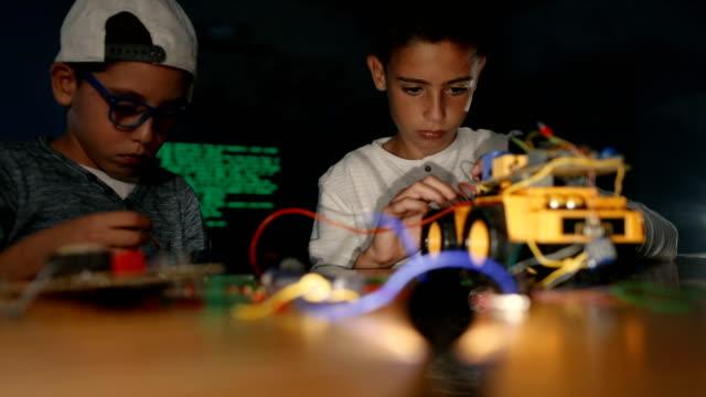 Boys assembling robotics together