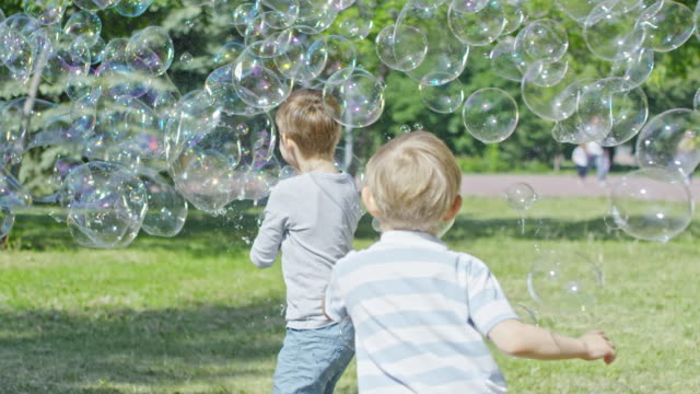 Boys Catching Giant Soap Bubble during Bubble Performance in Park video