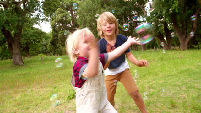 Boys having fun running after bubbles flying in park video
