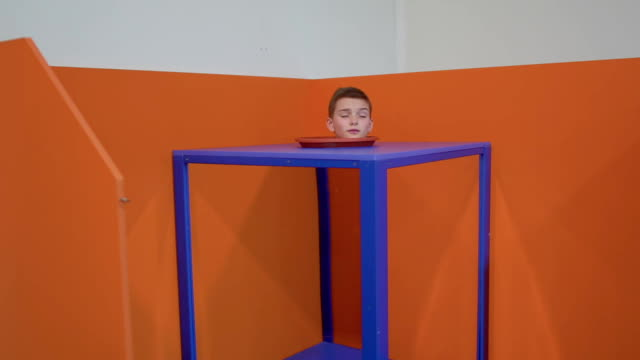 Boy's head inside the magic cube Boy's head inside the magic cube. The body of the boy is invisible. Magic trick with the disappearance of the body. Museum of popular science and technology. Prores codec. illusion stock videos & royalty-free footage