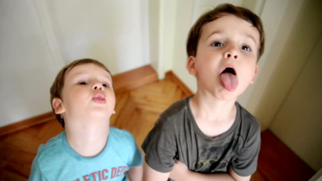 boys looking at camera and making faces - fare la lingua video stock e b–roll