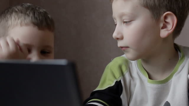 boys looking at the laptop video