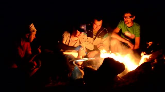 夜のキャンプファイアー近くの男の子 ビデオ