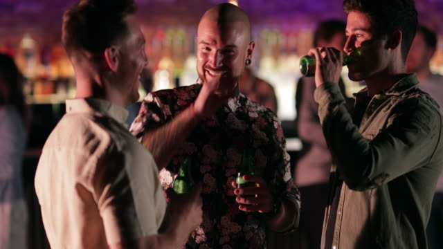 Boys Night Out Close up of mid-adult and young men talking and drinking beer in a bar/nightclub. bar counter stock videos & royalty-free footage