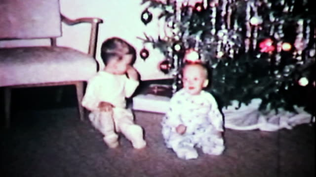 Boys Play In Front Of Christmas Tree-1965 Vintage 8mm film Cute little boys play around in front of the Christmas tree including getting scolded for touching the ornaments in 1965. 20th century stock videos & royalty-free footage