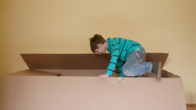 vídeos de stock e filmes b-roll de boys playing hide and seek game - cardboard box