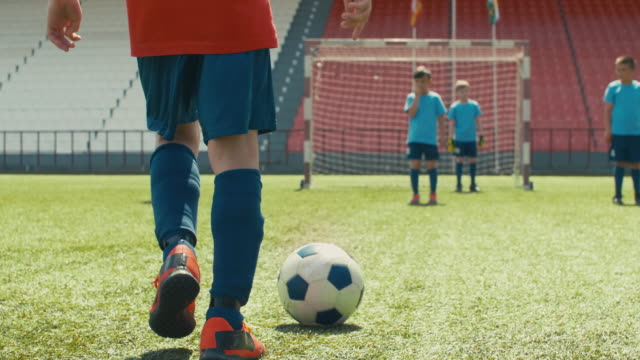 Boys playing professional soccer on stadium Tilt up shot of young soccer player dribbling ball through stadium, trying to shoot it, but miss the goal and hitting opposite player goal post stock videos & royalty-free footage