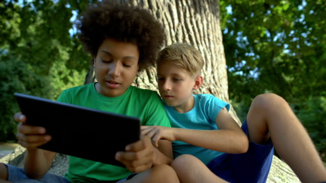 Boys playing tablet sitting under big tree in park, friends spending free time