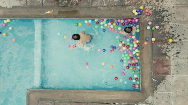 Jungen spielen mit Bällen am Pool in Mexiko – Video