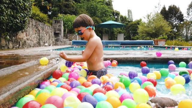 Jungs spielen mit Bällen am Pool in Mexiko. – Video