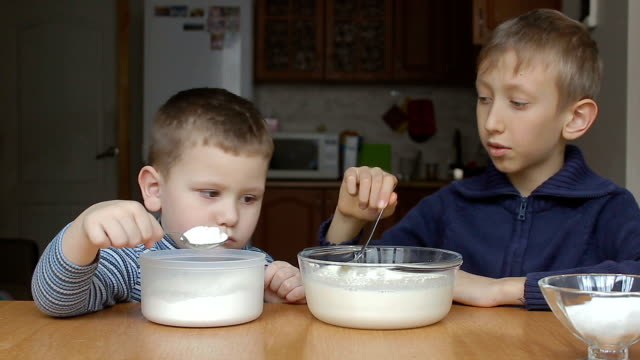 Boys prepare dough and younger boy add flour video