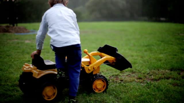 boys pretend to plant crops in village area - сельскохозяйственная машина стоковые видео и кадры b-roll