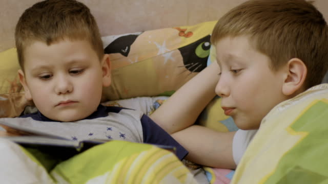 boys reading book at the bed video