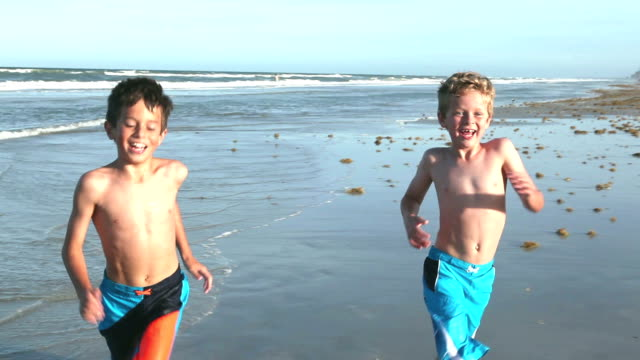 Boys running on sand and water at beach Two boys having fun at the beach, running across the wet sand and surf. They are brothers, 9 and 10 years old, wearing swim trunks. swimwear stock videos & royalty-free footage