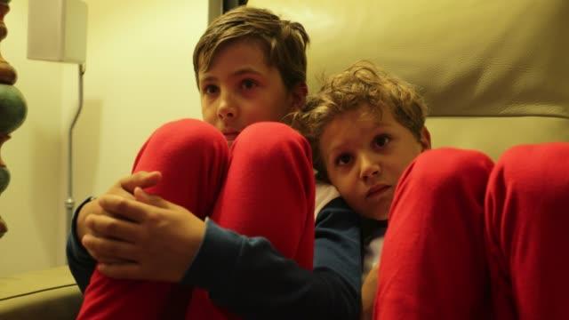 vídeos de stock e filmes b-roll de boys seated on sofa watching tv off camera. 4k candid clip of children watching screen at home - tv e familia e ecrã