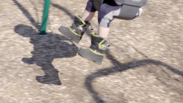 Boy's shadow on ground as he swings in playground video