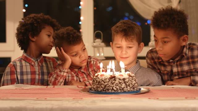 Boys sit near birthday cake. video