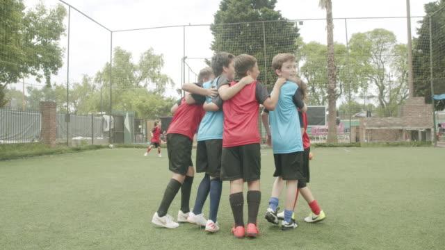 Boys standing arm around on soccer field video