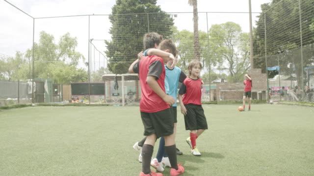 stockvideo's en b-roll-footage met jongens staande arm rond op voetbalveld - huddle