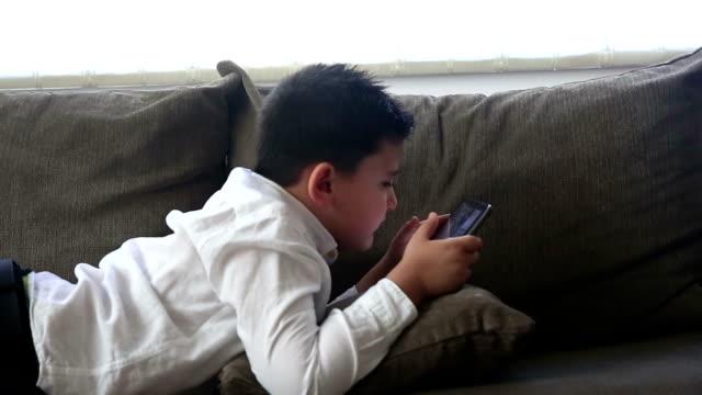 Boys using digital tablet together on sofa in living room - vídeo