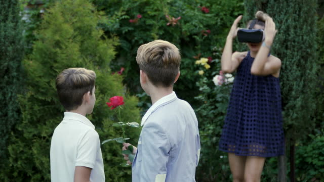 Boys want to present a rose to mother, but she's busy in virtual reality glasses video