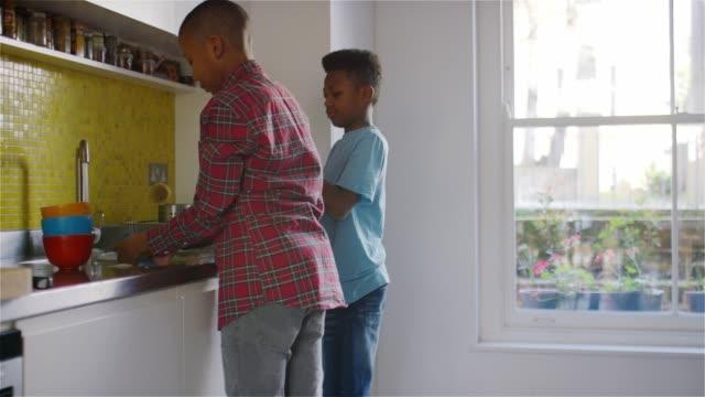 2 boys washing dishes at kitchen sink