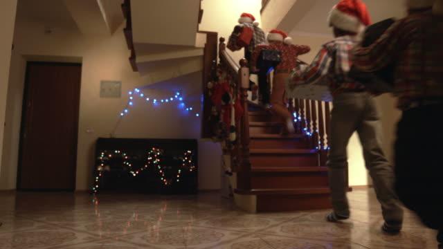 stockvideo's en b-roll-footage met jongens met presenteert uitvoeren naar boven. - christmas tree