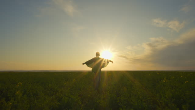 vídeos de stock e filmes b-roll de a boy-superhero in a green cloak is running across a field. the cloak is fluttering in the wind. sunset. 4k - baby super hero