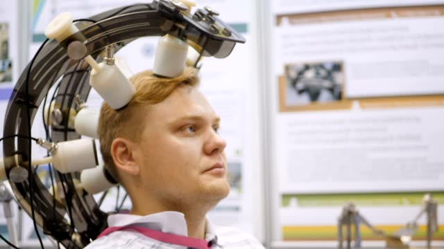Brain research. The power of thought. Man controls remotely with the help of the brain. Man wired to an EEG machine or electroencephalograph which produces a graphical record of electrical activity Man wired to an EEG machine or electroencephalograph which produces a graphical record of electrical activity of the brain. Young man set on his head. Electroencephalographic examination. electrode stock videos & royalty-free footage